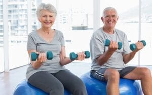 An old couple doing shoulder and arm exercises to relieve stiffness and pain