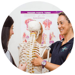 Woman shown explaining the skeletal structure of a human body to her student