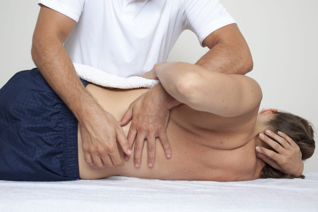 Photo of a therapist massaging a woman's lower back and spinal cord on the massage table